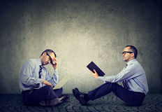 Due uomini che si siedono su un pavimento uno che legge un libro altro lavorare al computer portatile Immagine Stock Libera da Diritti