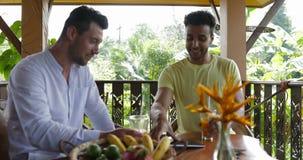 Due uomini che si siedono sul computer digitale di conversazione della compressa della tenuta del terrazzo di estate, coppia gay  stock footage