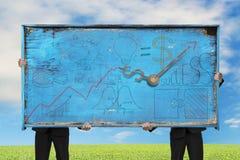 Due uomini che tengono il vecchio blu scarabocchia il tabellone per le affissioni sul cielo della natura Immagini Stock Libere da Diritti