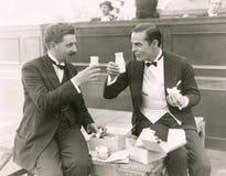 Due uomini che tostano con le bottiglie per il latte Immagini Stock Libere da Diritti