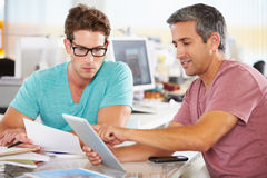 Due uomini che utilizzano il computer della compressa nell'ufficio creativo Immagini Stock Libere da Diritti
