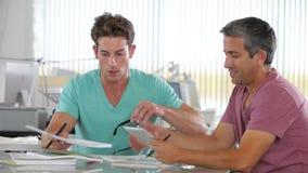 Due uomini che utilizzano il computer della compressa nell'ufficio creativo video d archivio