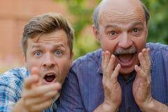Due uomini colpiti generano ed il figlio che esamina la macchina fotografica con la bocca aperta Fotografia Stock Libera da Diritti