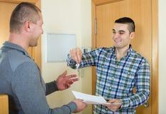 Due uomini con il contratto al gradino della porta dell'appartamento fotografia stock