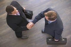 Due uomini d'affari all'interno che agitano le mani fotografia stock