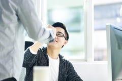 Due uomini d'affari asiatici che urtano i pugni in ufficio fotografia stock