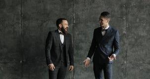 Due uomini d'affari attraenti è comunicano e ridono in un ufficio moderno del sottotetto stock footage
