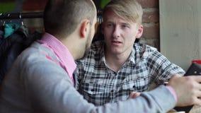 Due uomini d'affari bei che si siedono in caffè urbano e che discutono progetto importante archivi video