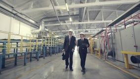 Due uomini d'affari che camminano attraverso la fabbrica stock footage
