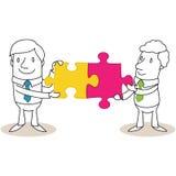 Due uomini d'affari che combinano due pezzi del puzzle Immagini Stock Libere da Diritti