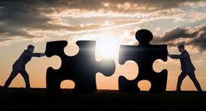 Due uomini d'affari che combinano i pezzi di puzzle Fotografie Stock Libere da Diritti