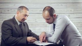 Due uomini d'affari che discutono i termini del contratto archivi video