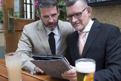 Due uomini d'affari che esaminano una compressa Immagine Stock Libera da Diritti