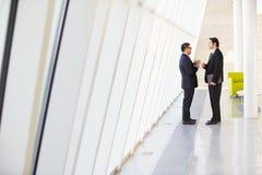 Due uomini d'affari che hanno riunione informale in ufficio moderno Fotografie Stock Libere da Diritti