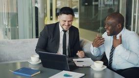 Due uomini d'affari che parlano il ANG che ride in caffè moderno Colleghi di affari divertendosi e scherzando esaminando computer video d archivio