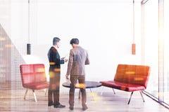 Due uomini d'affari che parlano in un ufficio rosso del sofà Immagine Stock