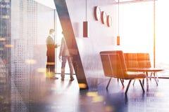 Due uomini d'affari che parlano in un ufficio rosso del sofà parteggiano Fotografie Stock Libere da Diritti