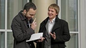 Due uomini d'affari che si incontrano fuori dell'edificio per uffici stock footage