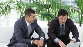 Due uomini d'affari che si siedono sul sofà facendo uso di un computer portatile archivi video