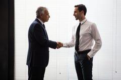 Due uomini d'affari che stanno su e che stringono le mani Immagine Stock Libera da Diritti