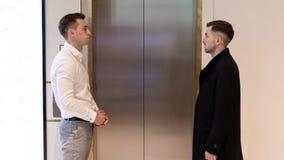 Due uomini d'affari che stanno vicino all'elevatore Gente di affari vicino ad un elevatore in ufficio fotografia stock