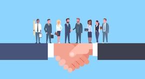 Due uomini d'affari che stringono le mani con Team Of Businesspeople, accordo di affari ed il concetto di associazione royalty illustrazione gratis