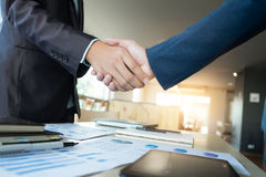 Due uomini d'affari che stringono le mani nel corso di una riunione nell'ufficio, s fotografie stock
