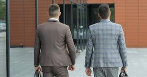 Due uomini d'affari chiacchierano insieme mentre camminano avanti attraverso un edificio per uffici moderno occupato Isolato su b archivi video