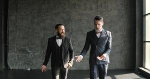 Due uomini d'affari chiacchierano insieme mentre camminano avanti attraverso un ufficio moderno del sottotetto stock footage