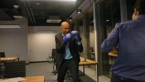 Due uomini d'affari competitivi che combattono con i guantoni da pugile in ufficio corporativo video d archivio