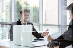 Due uomini d'affari con il computer portatile sulla riunione d'affari Fotografia Stock Libera da Diritti