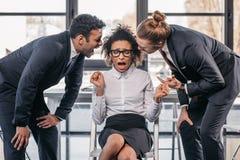 Due uomini d'affari emozionali in formalwear che gridano sulla donna di affari in ufficio Immagini Stock Libere da Diritti