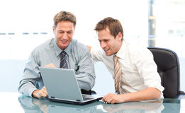 Due uomini d'affari felici che lavorano insieme su un computer portatile Fotografia Stock Libera da Diritti