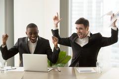 Due uomini d'affari felici che sollevano le mani si avvicinano al computer portatile, celebrante il suc Fotografia Stock