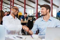 Due uomini d'affari felici che stringono le mani e che lavorano nell'ufficio Immagine Stock Libera da Diritti