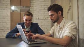 Due uomini d'affari hanno letto le notizie e la chiacchierata nel servizio della rete sociale sull'aggeggio moderno stock footage
