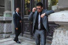 Due uomini d'affari, occhiali da sole, vicino alle porte della costruzione Fotografie Stock