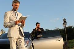Due uomini d'affari si avvicinano all'automobile, al iPad ed alla cellula di lusso Pho Immagini Stock