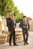 Due uomini d'affari si avvicinano alla fontana, occhiali da sole Immagini Stock Libere da Diritti