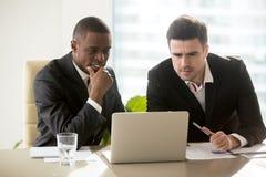 Due uomini d'affari sulla riunione che esamina lo schermo del computer portatile, premuroso fotografia stock