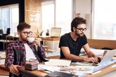Due uomini delle free lance che lavorano al computer portatile ed al caffè bevente allo scrittorio Fotografia Stock Libera da Diritti
