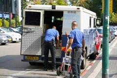 Due uomini delle guardie del camion della Company di Brink hanno messo le borse dei soldi nell'automobile guardie che trasportano immagine stock