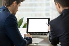 Due uomini di affari che esaminano derisione sullo schermo in bianco del computer portatile Immagine Stock Libera da Diritti