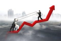 Due uomini di affari che muovono la linea di tendenza rossa ascendente del simbolo di dollaro Fotografie Stock Libere da Diritti