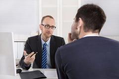 Due uomini di affari che si siedono nell'ufficio: riunione o intervista di lavoro Immagini Stock