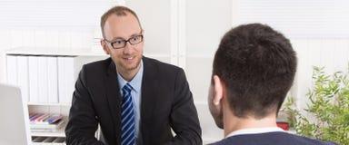 Due uomini di affari che si siedono nell'ufficio: riunione o intervista di lavoro Fotografia Stock