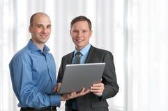 Due uomini di affari con il computer portatile Immagine Stock Libera da Diritti