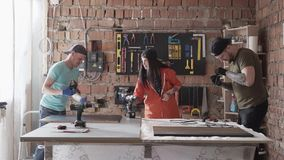 Due uomini e donna che lavorano in vestiti comodi e cappucci che fanno mobilia nell'officina Fabbricazione moderna della gente stock footage