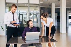 Due uomini e una donna che lavora nel centro del numero Immagini Stock
