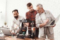 Due uomini hanno installato una stampante 3d, le tenute anziane di un uomo un computer portatile in sue mani e gli orologi il pro Immagini Stock